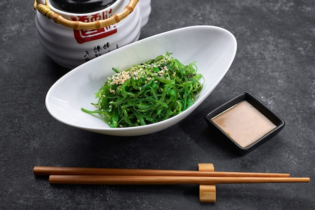 Chuka salade met komkommers, sesamzaadjes en saus, in een wit bord, met een japanse theepot, stokjes en esdoornbladeren, op zwart beton