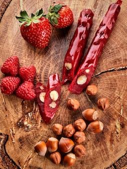 Churchkhela, aardbeien en noten snijden op een houten achtergrond, bovenaanzicht, serveren