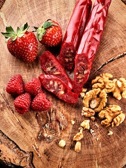 Churchkhela, aardbeien en noten snijden op een houten oppervlak, bovenaanzicht, serveren