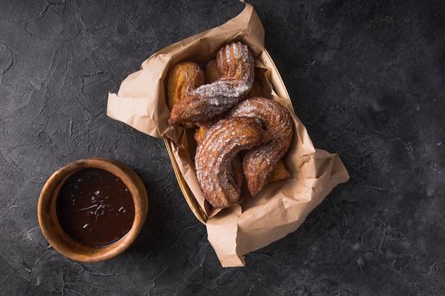 Churros in een papieren zak met suiker en chocoladesaus op zwart