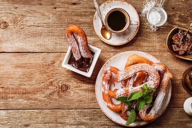 Churros koffie en warme chocolademelk op houten tafelblad bekijken