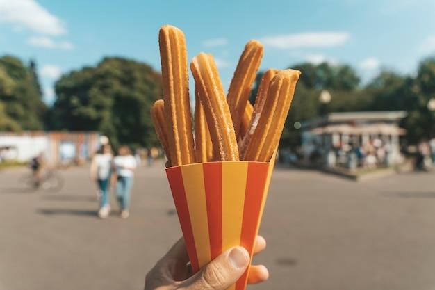 Churros wafels in de hand op straat churros street food dessert gemaakt van deeg en suiker fast food...