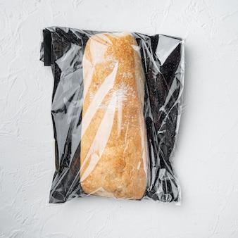 Ciabatta panini brood in een plastic zak, op witte achtergrond, bovenaanzicht plat lag