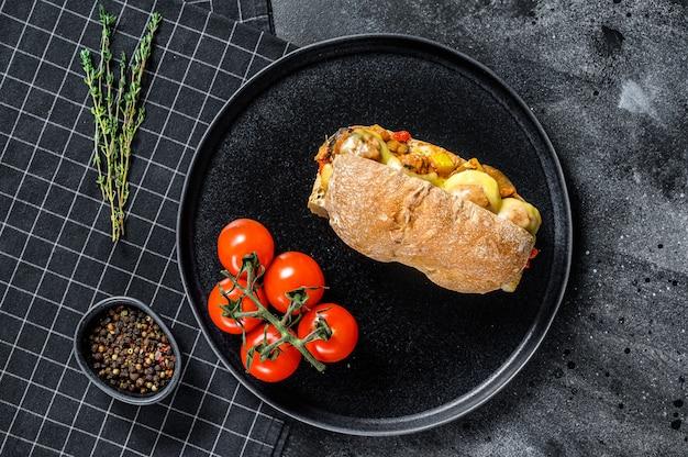 Ciabatta sandwich met gehaktballetjes, kaas en tomatensaus. zwart oppervlak. bovenaanzicht