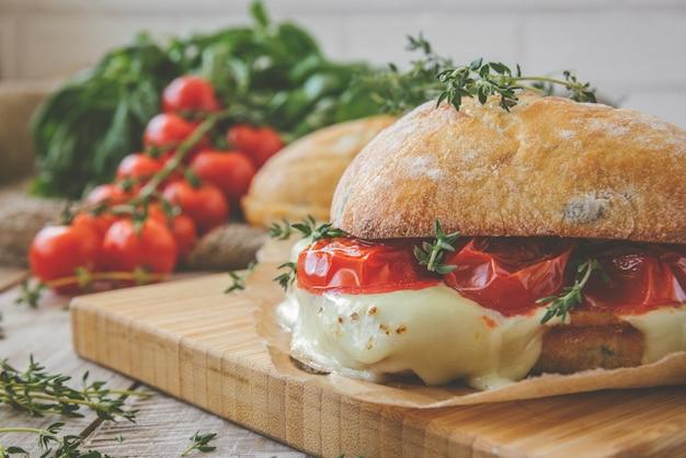 Ciabattasandwich met tomaten, kruiden en olie op geroosterd knoflookkaasbrood. afgezwakt.