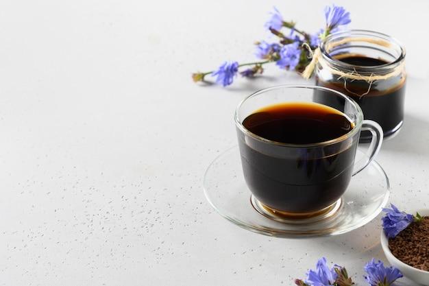 Cichorei wortel koffie in glazen beker en verse bloemen. gezondheidsvoordelen. kopieer ruimte. detailopname.