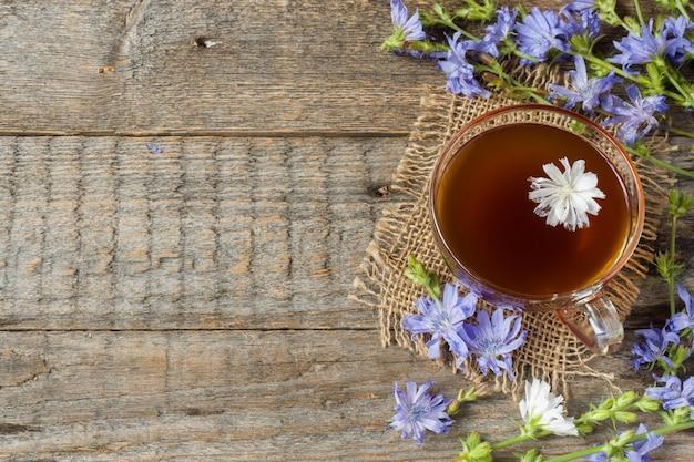 Cichoreydrank in kop en bloemen op rustieke houten achtergrond. geneeskrachtige plant cichorii.