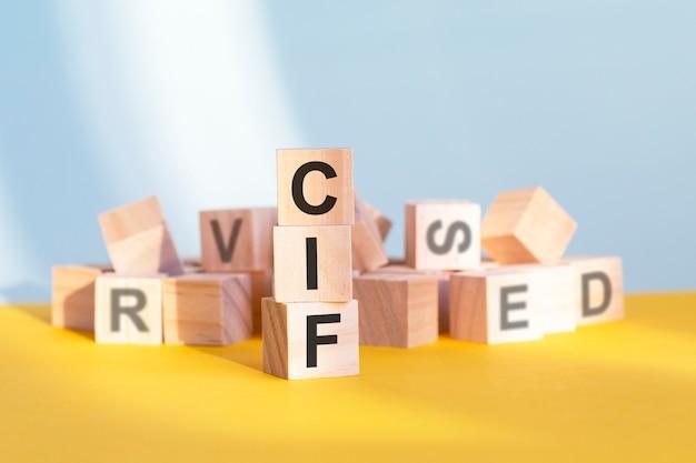 Cif geschreven op houten kubussen - gerangschikt in een verticale piramide, grijze en gele achtergrond, cif - afkorting voor kostenverzekering en vracht, bedrijfsconcept