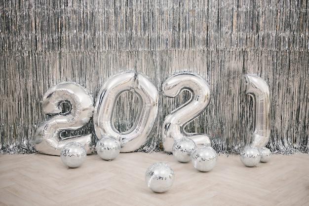 Cijfers 2021 van zilverkleurige ballen tegen een zilveren muur. nieuwjaar