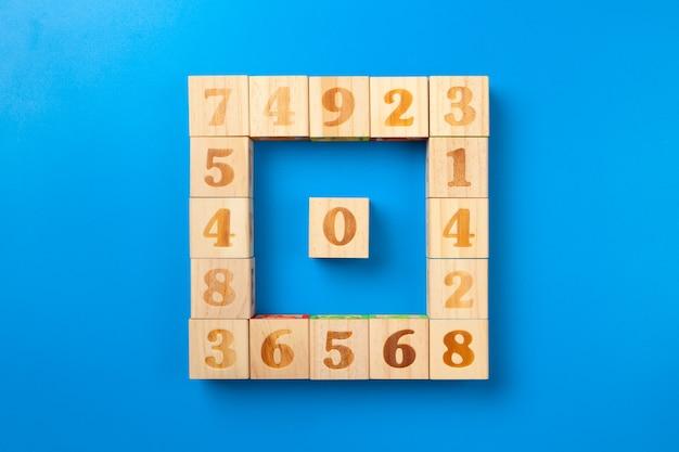 Cijfers, houten kleurrijke alfabetblokken op blauw, plat lag, bovenaanzicht,