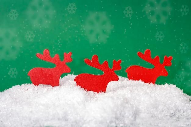 Cijfers van houten kerstherten in de sneeuw op een groene achtergrond met sneeuwvlokken.