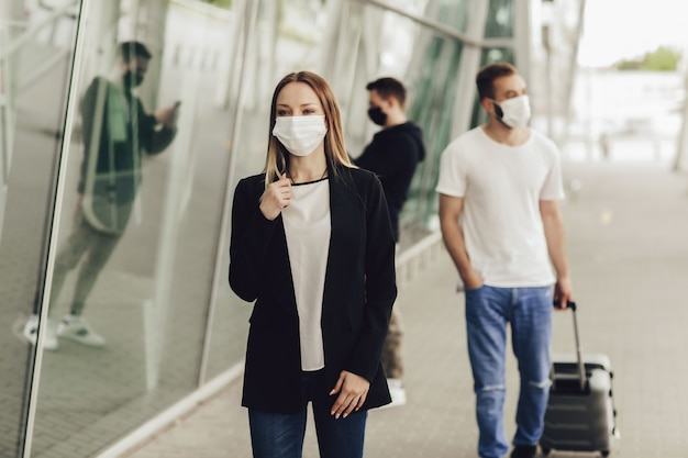 Cijfers van jongeren in beschermende maskers in de buurt van de luchthaven. veilig reizen tijdens een pandemie. vliegtuigreizen, quarantaine en pandemisch concept