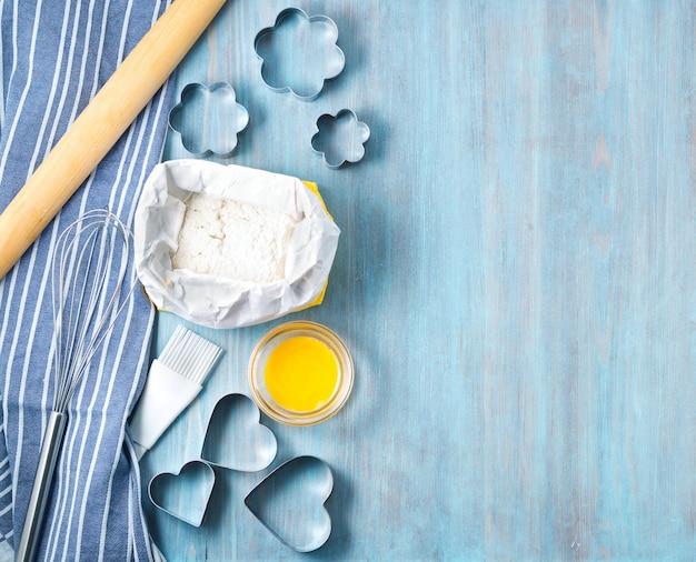 Cijfers voor het bakken van gesneden metalen mal, deegroller, bloem op blauwe houten tafel