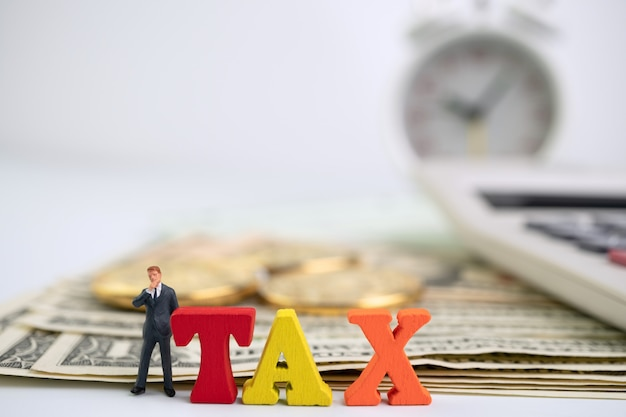 Cijferzakenman die zich naast houten belastingwoord op bankbiljet en gouden muntstuk en calculator bevinden