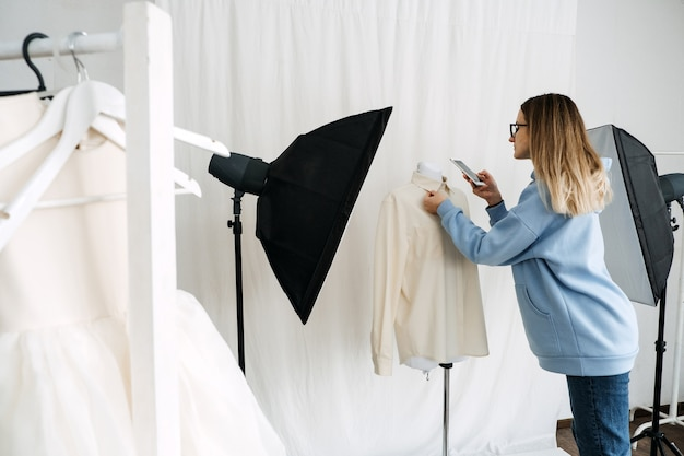Circulaire economie tweedehands fast fashion duurzame mode winkeleigenaar die foto's maakt van tweedehands