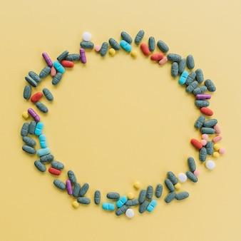 Circulaire frame gemaakt met kleurrijke pillen op gele achtergrond