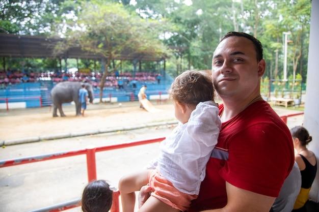 Circus met dieren. papa houdt de peuter in zijn armen tegen de achtergrond van de show en glimlacht naar de camera.