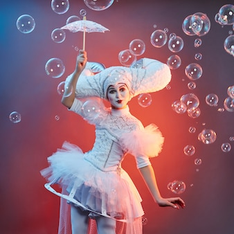 Circus performer goochelaar toont trucs met zeepbellen. de vrouw en een meisje blazen zeepbels in circus op tonen