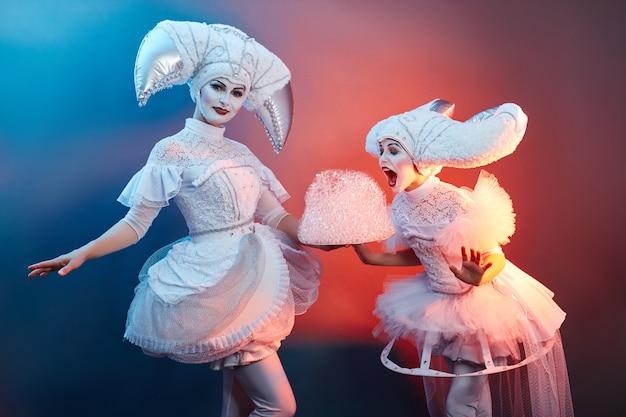 Circus performer goochelaar toont trucs met zeepbellen. een vrouw en een meisje blazen zeepbellen op in het circus