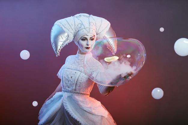 Circus performer goochelaar toont trucs met zeepbellen.