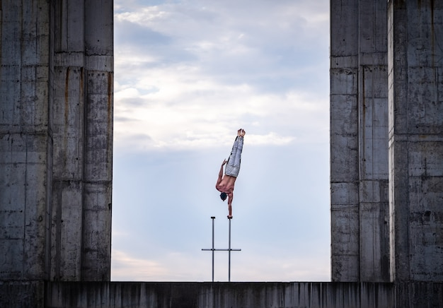 Circusartiest houdt het evenwicht aan de ene kant op de achtergrond van de lucht en de industriële constructie