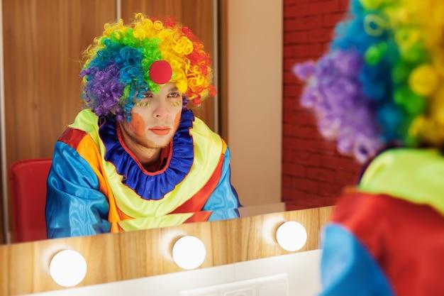 Circusclown kijkt in een spiegel in de make-upruimte.