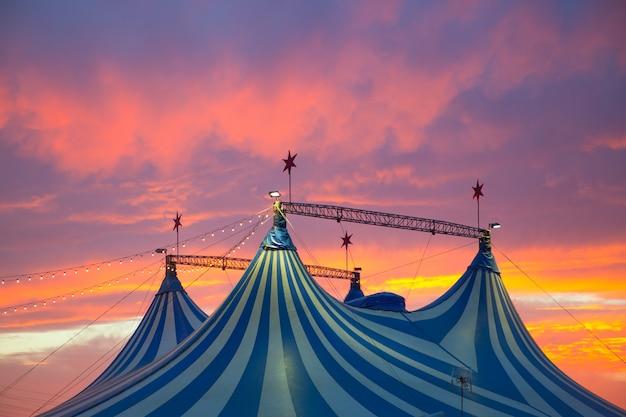 Circustent in een dramatische kleurrijke zonsonderganghemel