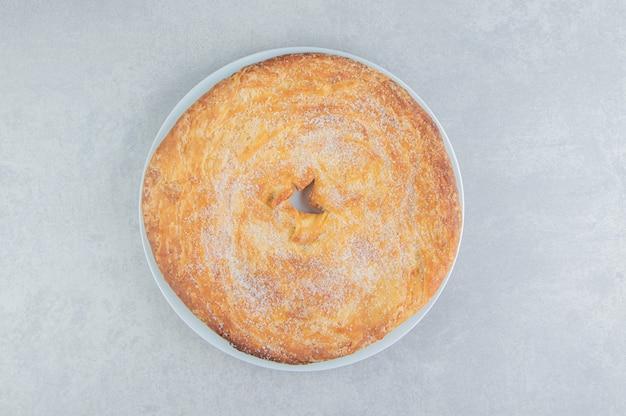 Cirkel gebak versierd met poeder op witte plaat.