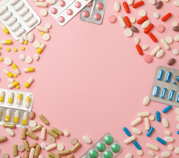 Cirkel gemaakt van pillen op roze, ruimte voor tekst