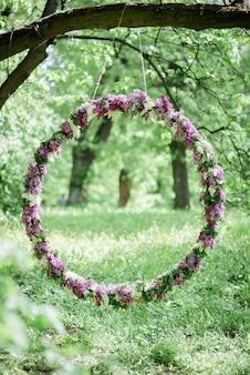 Cirkel gemaakt van violet en witte lila hangt aan de boom