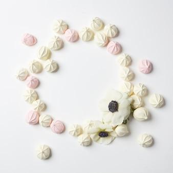 Cirkel van handgemaakte zoete roze en witte zephyr marshmallow. hart kleine snoepjes op witte achtergrond.