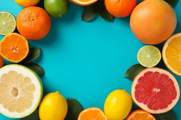 Cirkel van sappige citrusvruchten op turkooizen achtergrond, ruimte voor tekst