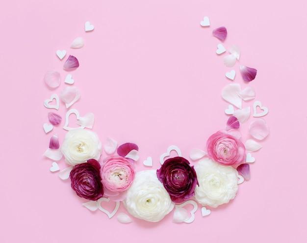 Cirkelframe gemaakt van ranonkelbloemen, bloemblaadjes en harten op een lichtroze bovenaanzicht