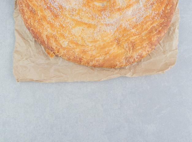 Cirkelgebak versierd met wit poeder op blad.