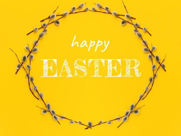 Cirkelkrans met een wilgentak met knoppen en tekst happy easter op een gele. voorjaarsvakantie en symbool van palmzondag in april.