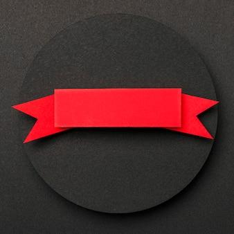 Cirkelvormige geometrische vorm van zwart papier en rood lint