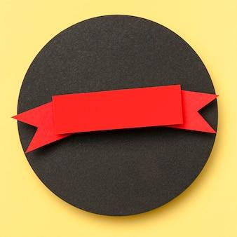 Cirkelvormige geometrische vorm van zwart papier op gele achtergrond