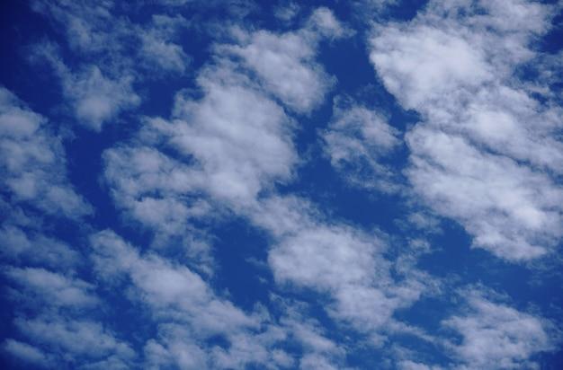 Cirrocumulus en altocumulus pluizige wolken op lichtblauwe hemelachtergrond.