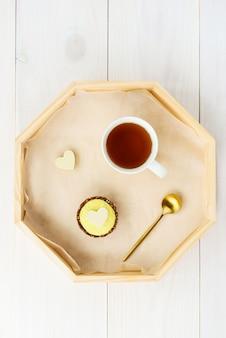 Citroen cashew cake met witte chocolade hart en een kopje thee op een houten dienblad.