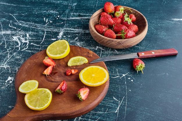 Citroen en aardbeien in een houten bord.