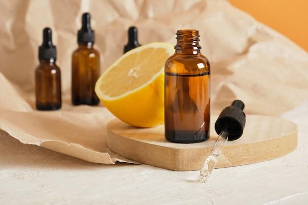 Citroen en bruine glazen fles met druppelaar voor serum of cosmetische olie op een houten podium in de vorm van een hart, milieuvriendelijk lichaamsverzorgingsconcept