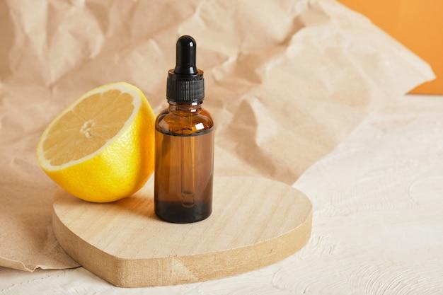 Citroen en bruine glazen fles met druppelaar voor serum of cosmetische olie op een houten podium in de vorm van een hart,