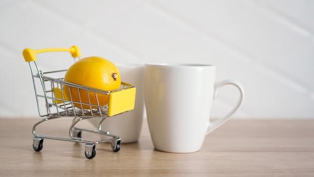 Citroen in een klein winkelwagentje op de keukentafel. vlakbij staat een witte mok thee. lichte en moderne keukenachtergrond.