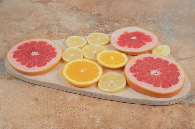Citroen, sinaasappel en grapefruit plakjes op een houten bord.
