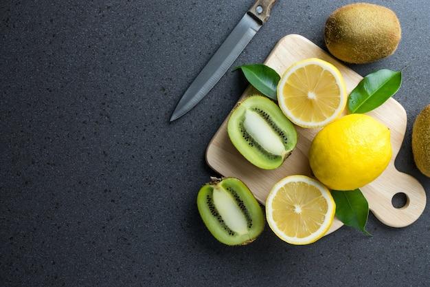 Citroenen en kiwivruchten met mes en houten scherpe raad