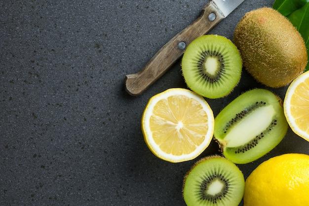 Citroenen en kiwivruchten staan op de zwarte keukentafel.