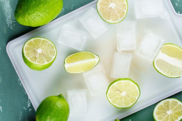 Citroenen en segmenten met ijsblokjes close-up op gips en snijplank