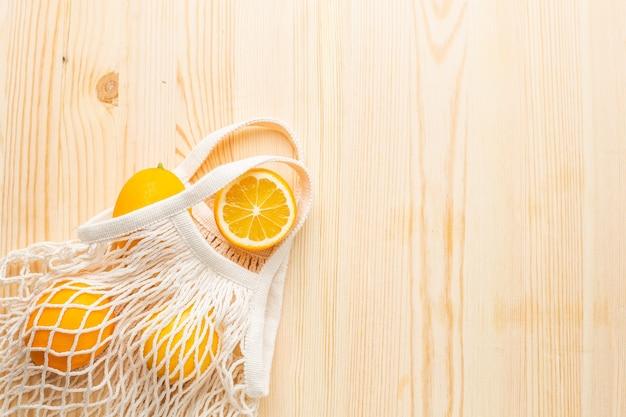 Citroenen in katoen eco vriendelijke tas winkelen op houten achtergrond. hulp bij verkoudheid, natuurlijke remedies tegen de ziekte
