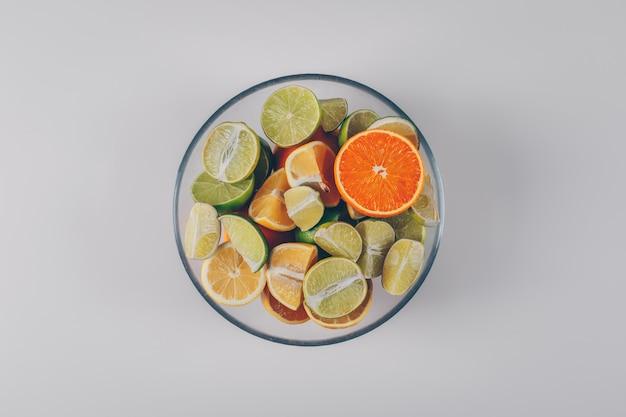Citroenen met groene citroenen en sinaasappel in een kom op witte achtergrond, bovenaanzicht.