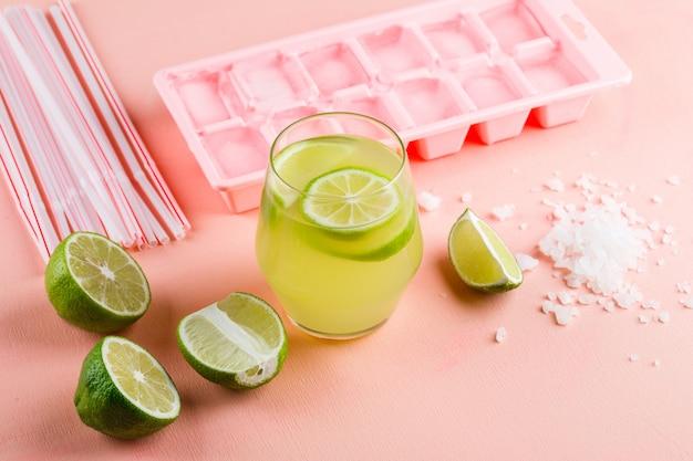 Citroenen met limonade, zout, ijs lade, rietjes hoge hoek uitzicht op een roze